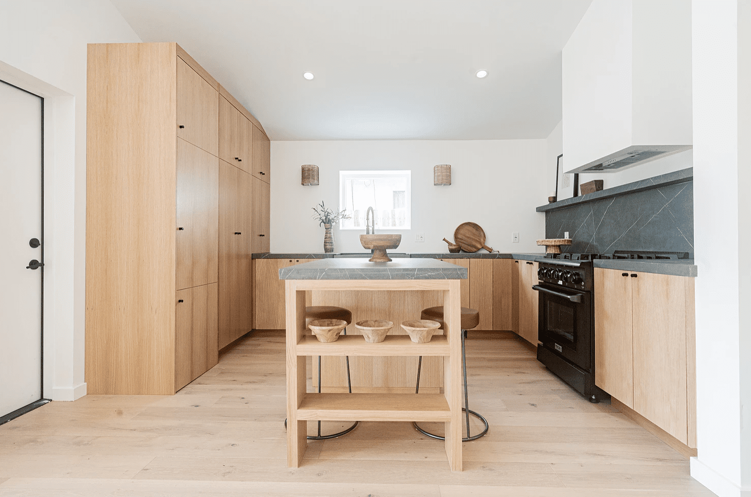 An open-concept kitchen lined with natural wood and charcoal marble