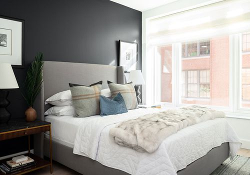 bedroom with black accent wall and gray bed