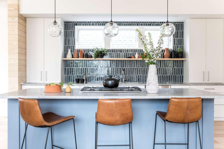 A kitchen with a blue island and black tiled backsplash
