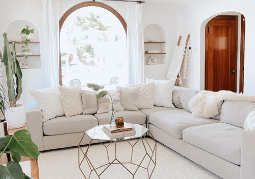 Pretty living room with cream colored sofa and boho accents.