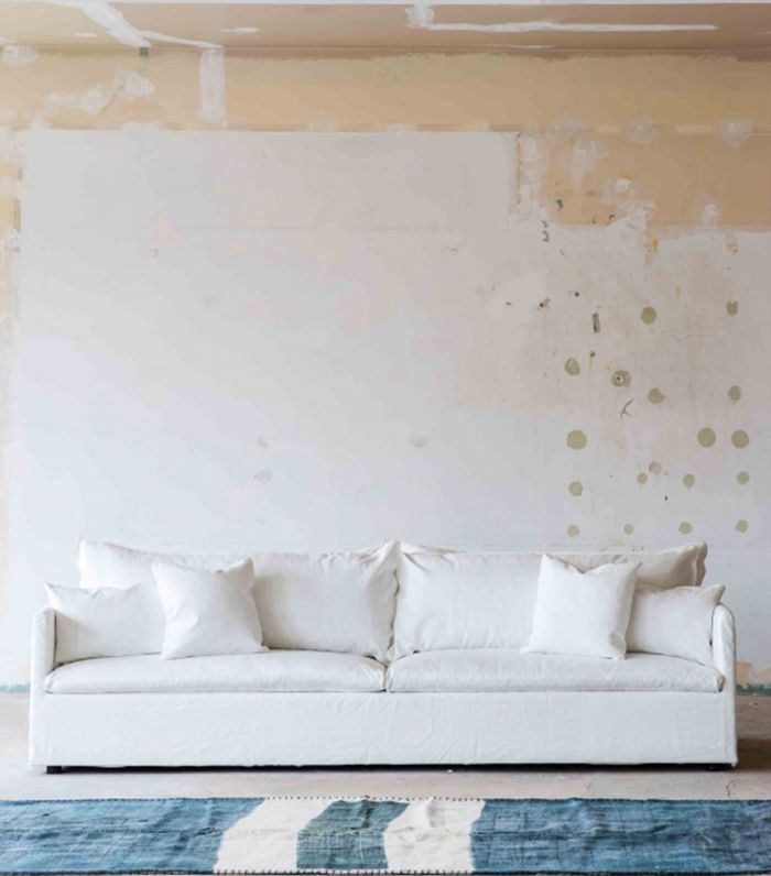 A white, linen 4-seater sofa with loose pillows.