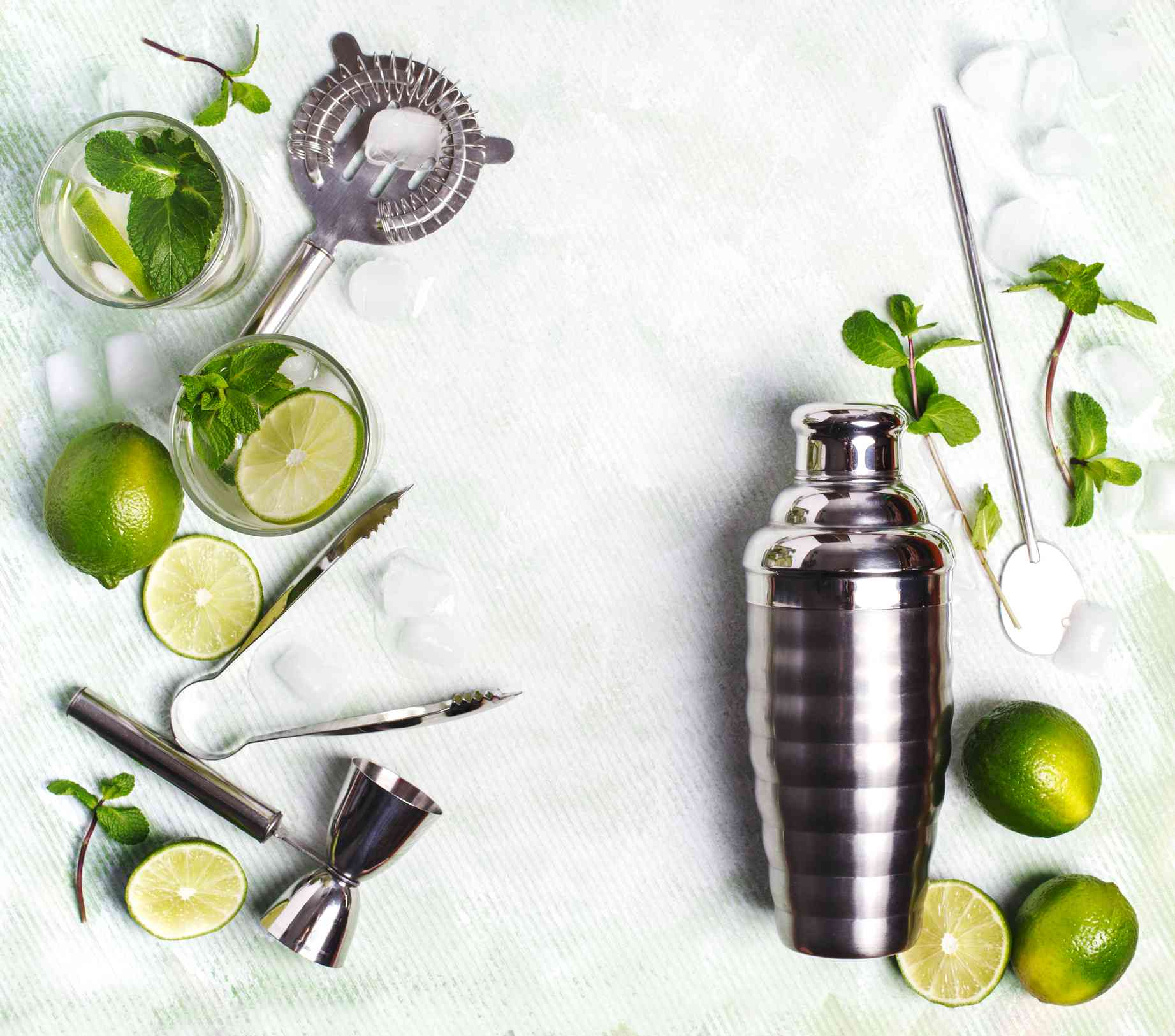Coctelera rodeada de limones y herramientas de barra.