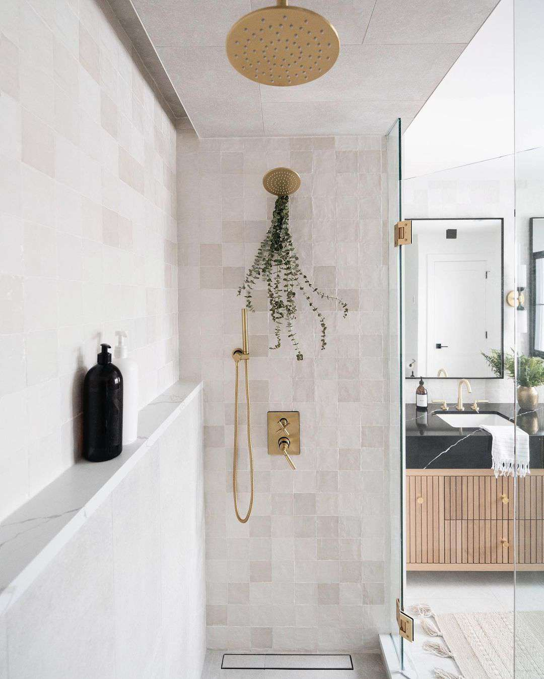 Shower with a glass door and gold faucet