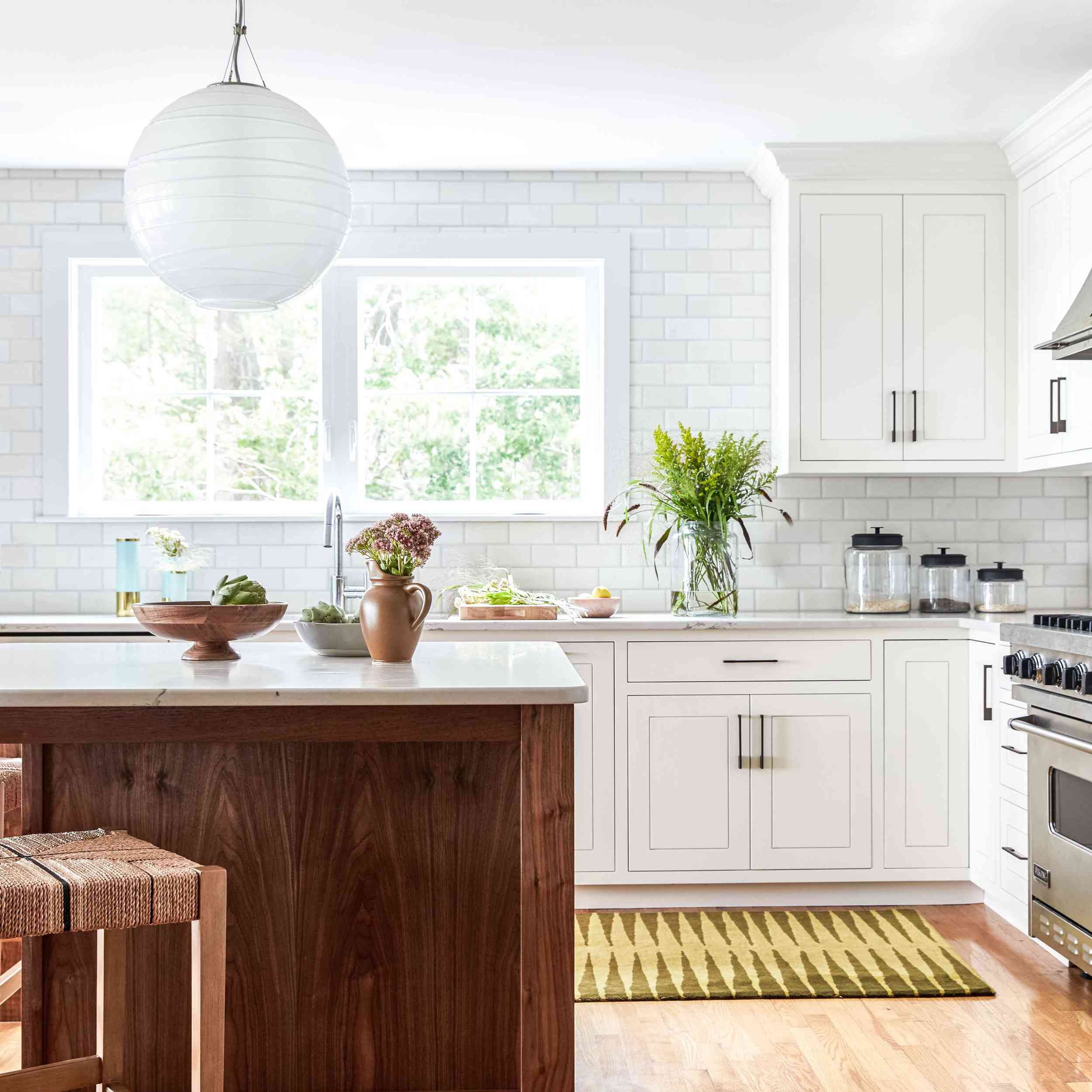 An open-concept kitchen with white cabinets and a yellow printed rug