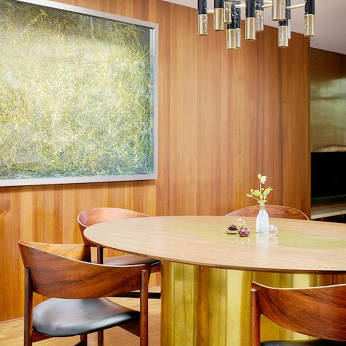 Green textured hanging artwork complements metallic accents of a dining room