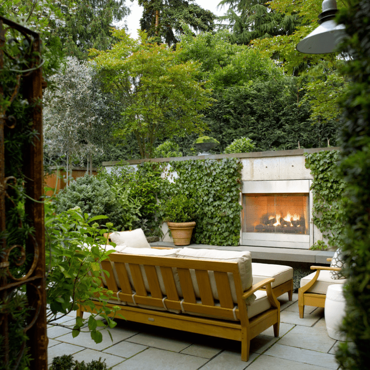 An outdoor fireplace overrun with lush vines