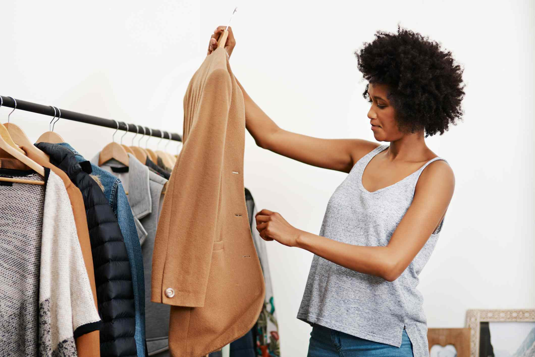 Woman holds up coat on a hanger