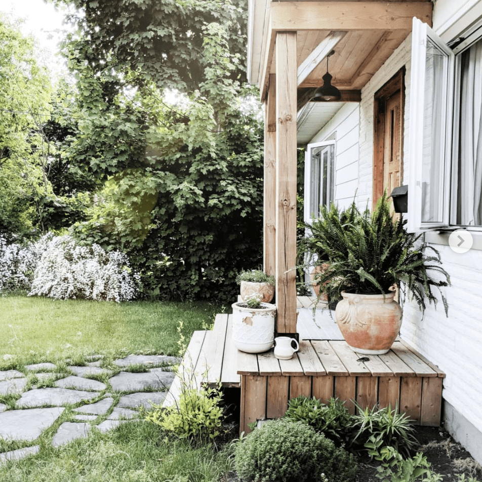Outdoor front porch with green landscaping.