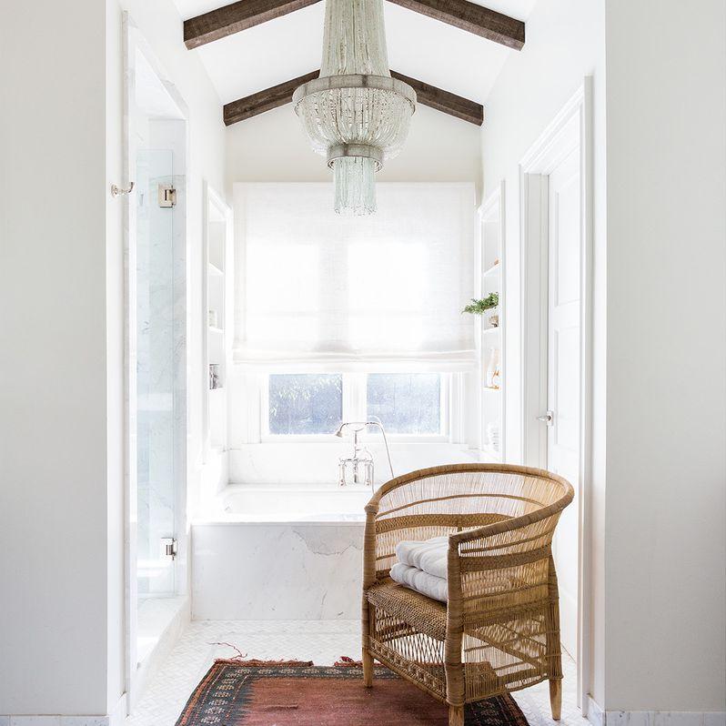 Bright bathroom with marble tub, wood beams, and vintage furnishings