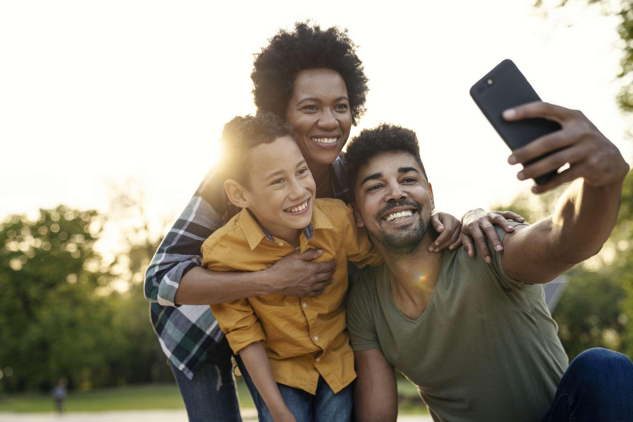 Familia joven se toma selfie en un entorno similar a un parque
