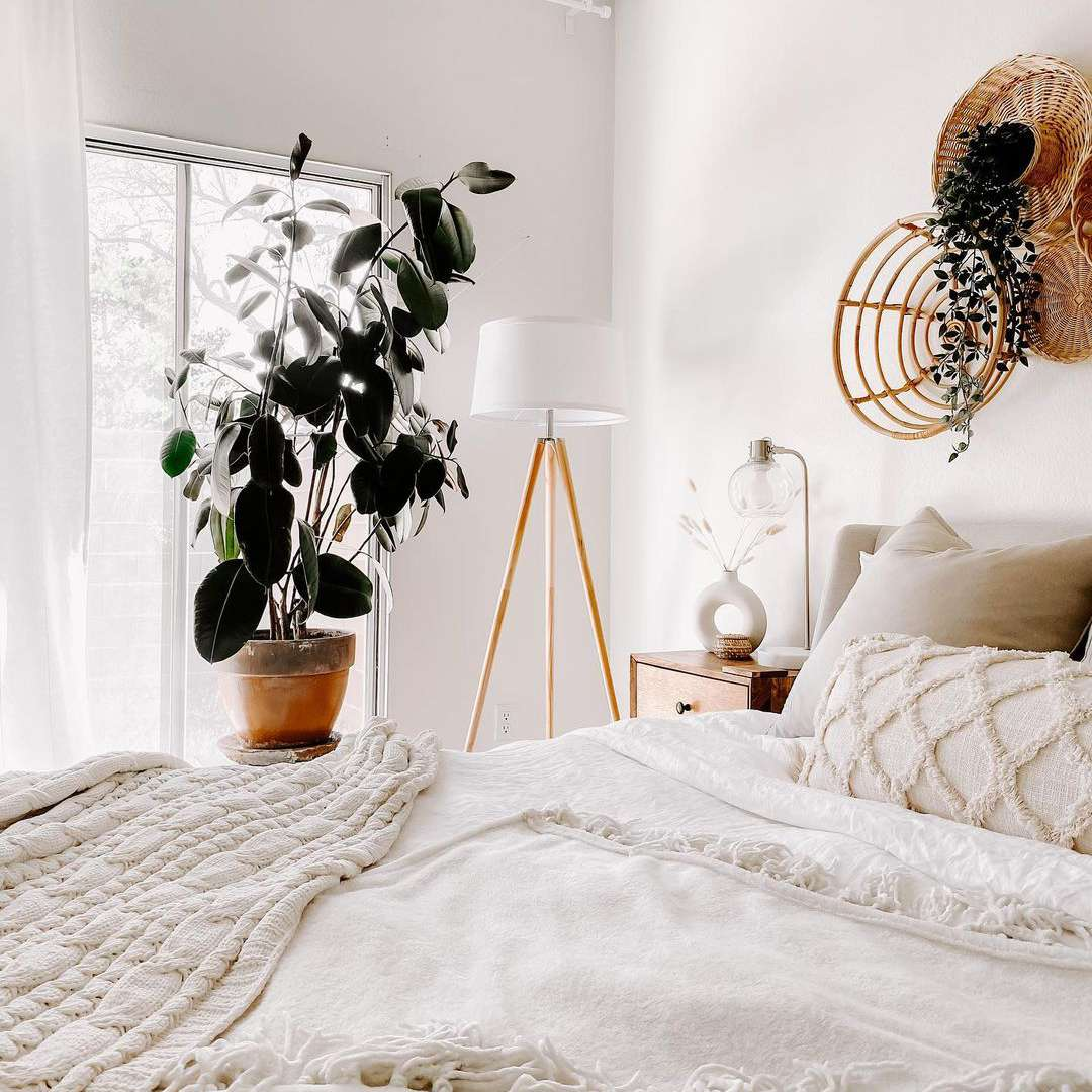 White bedroom with baskets behind the bed