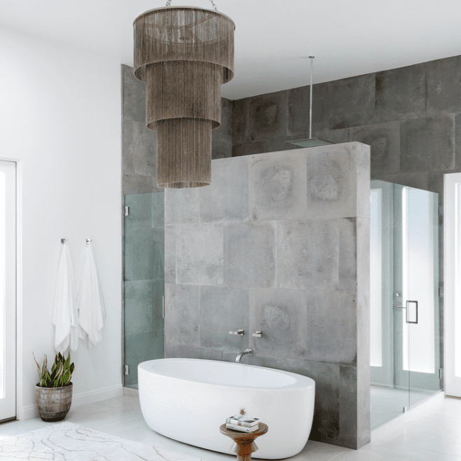A concrete bathroom with a bold tiered chandelier