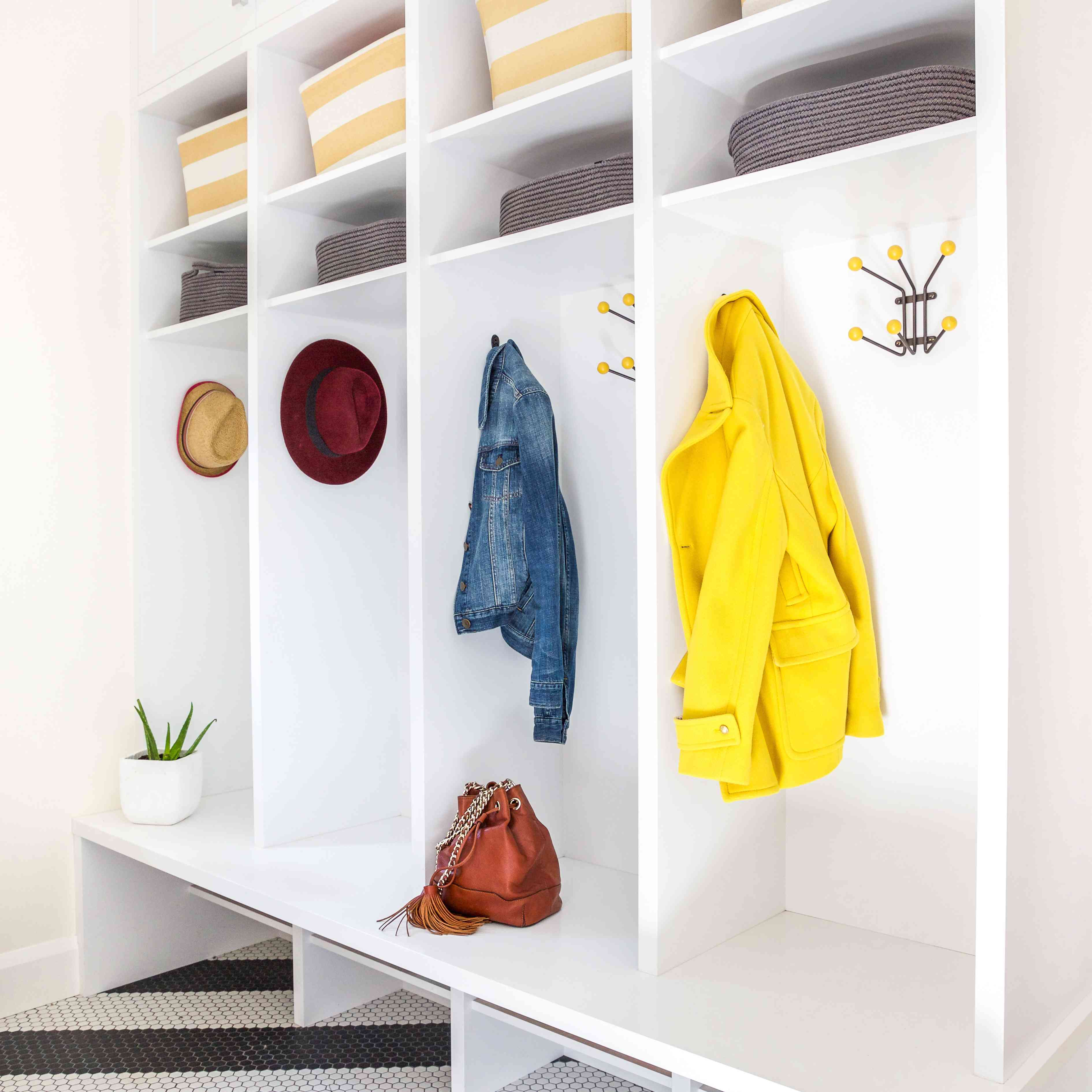 An all-white mudroom filled with yellow hooks and baskets