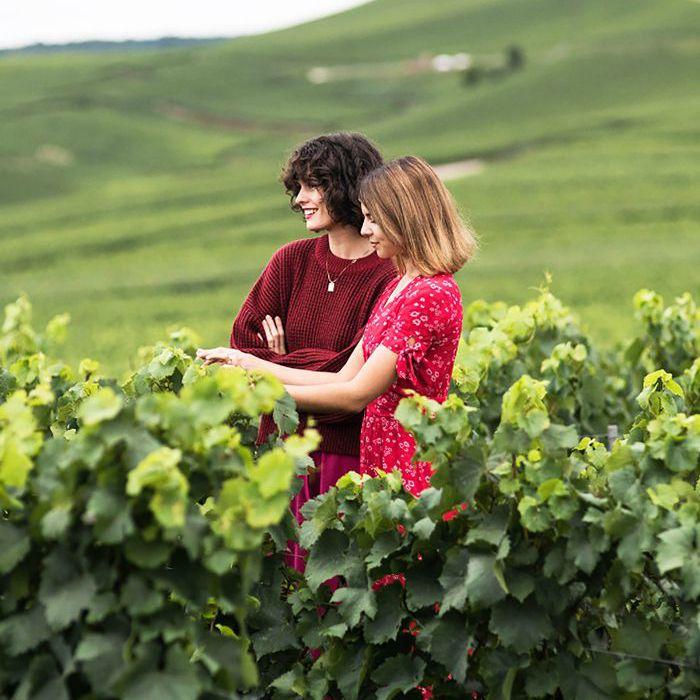 Dos mujeres jóvenes se paran en medio de un viñedo