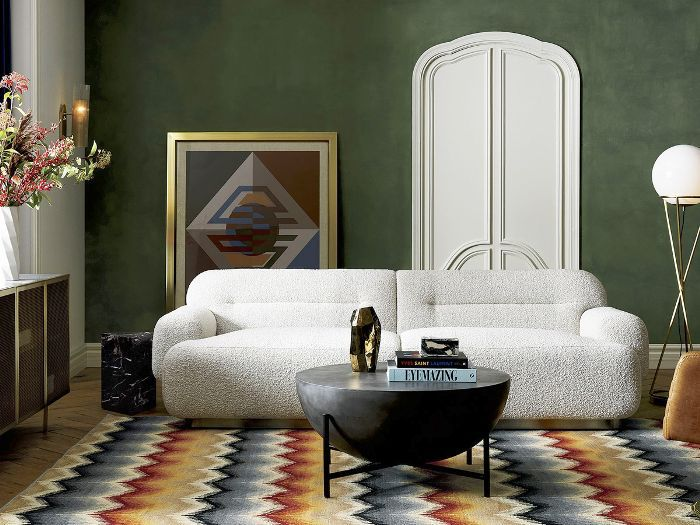 a living room with deep green walls and colorful rug
