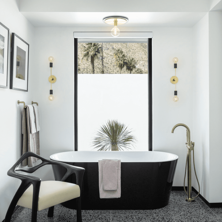 A bathroom with a black tub and charcoal terrazzo floors