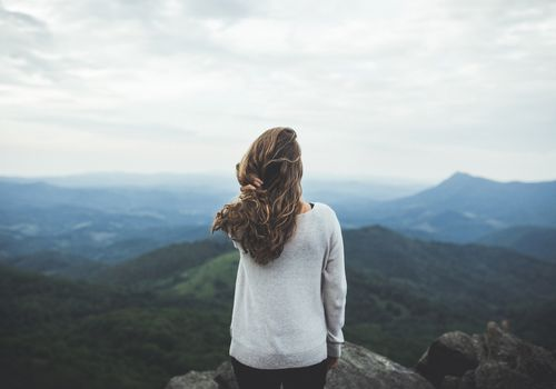 Girl standing at the top of a mountain.