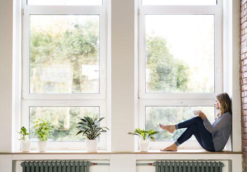 woman sitting by window drinking coffee