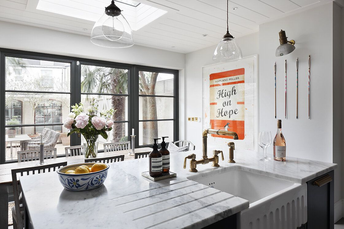 A light-filled kitchen with a rustic ceramic farmhouse sink