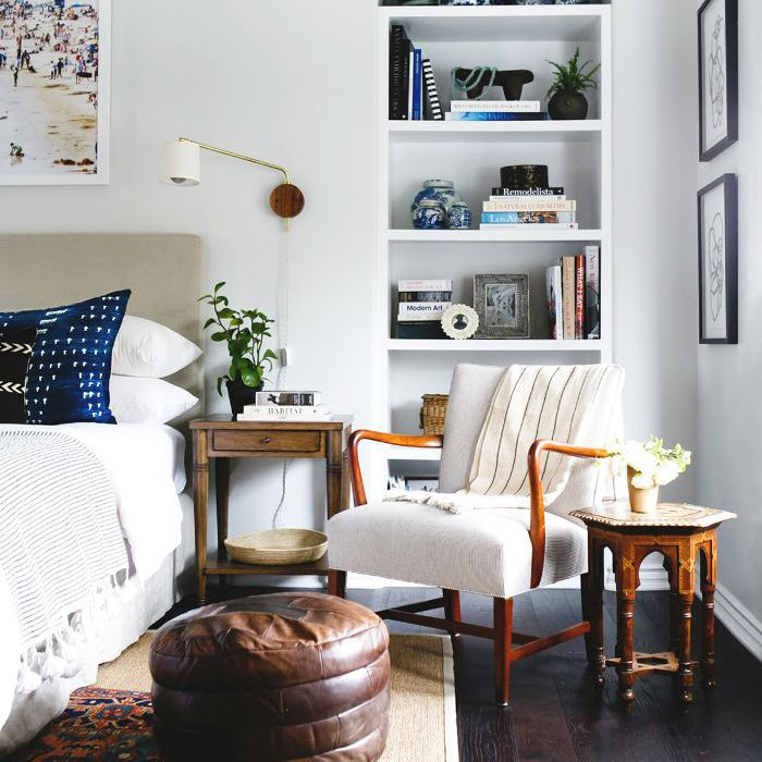 Lighting Tips: Sconces in a bedroom with built-in bookcase and white accent chair