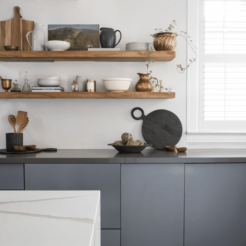 A kitchen with slate gray cabinets and exposed wooden shelves