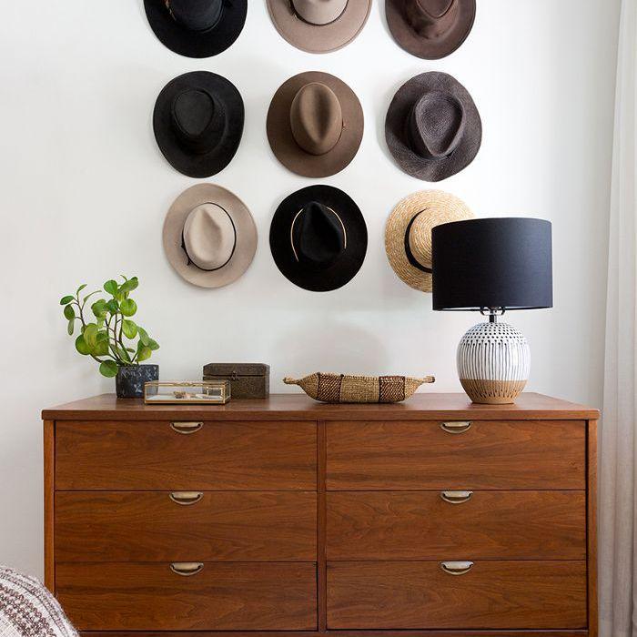 una pared de sombreros encima de una cómoda