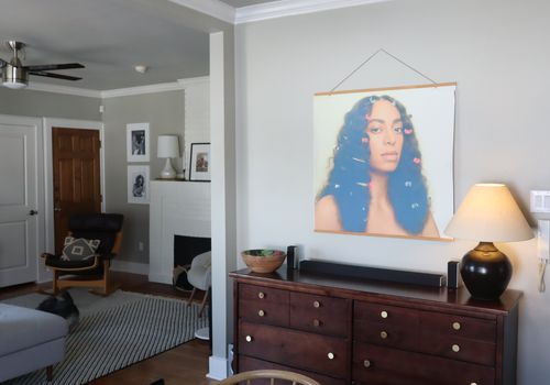 Overview of entryway and living room with Solange poster.