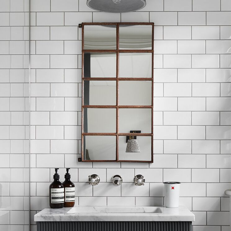 A bathroom with white subway tiles and a bold geometric mirror