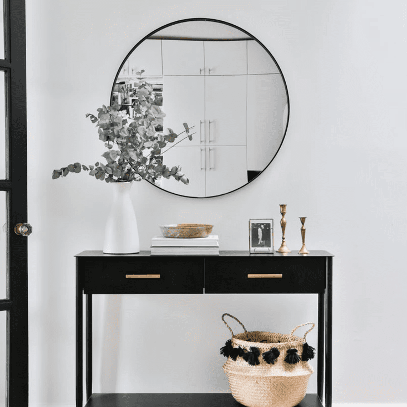 A sleek black console table adorned with minimal white and gold decor