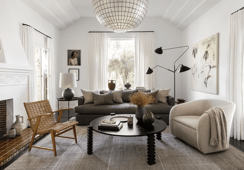 Neutral, sophisticated living room with overhead lighting and side table lamp.
