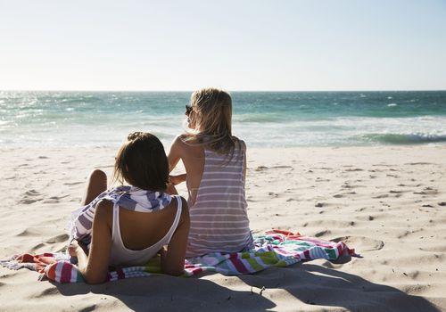 Pareja sentada en la playa durante un día soleado.