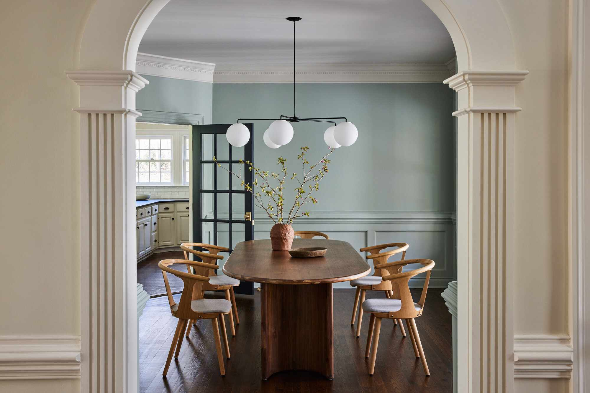 A dining room with sleek wooden furniture and light blue walls