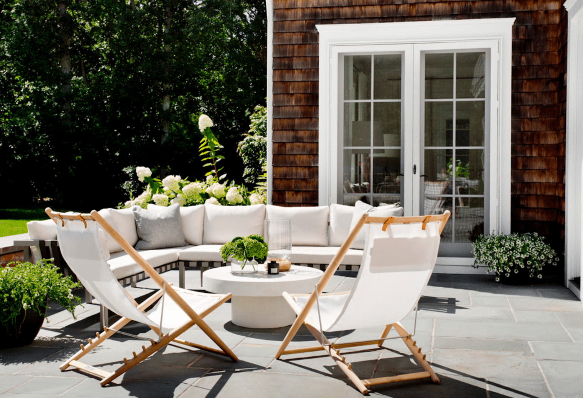 An outdoor deck with a large couch and two smaller chairs