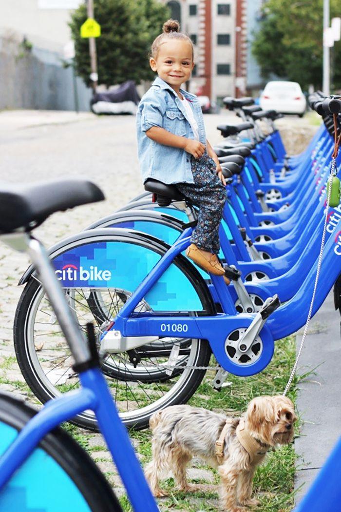 a girl on a bike and a dog on a leash