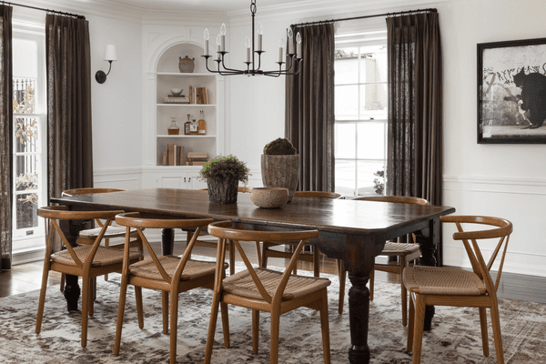 A dining room with wooden furniture and chocolate brown curtains