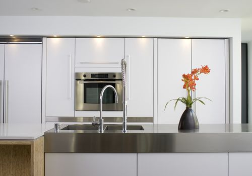 Modern white kitchen with stainless steel counter and oven