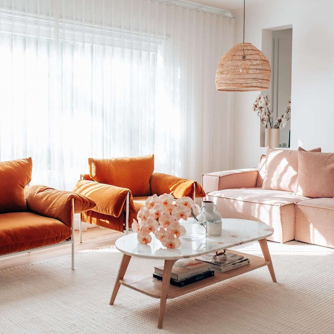Living room with pink sofa and orange chairs.