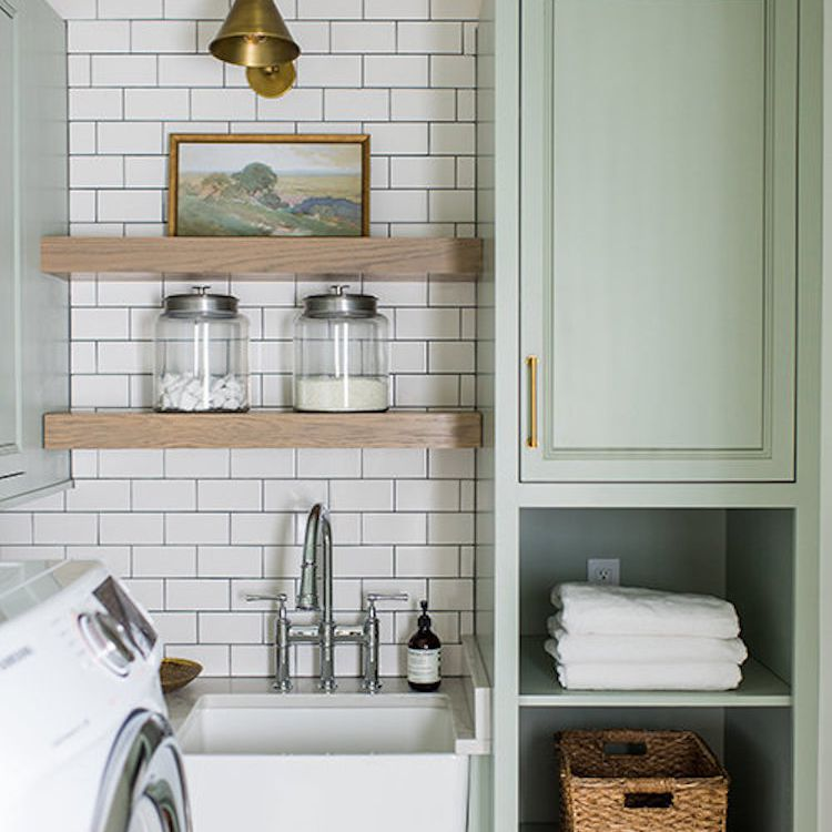 A laundry room with sea foam green cabinets