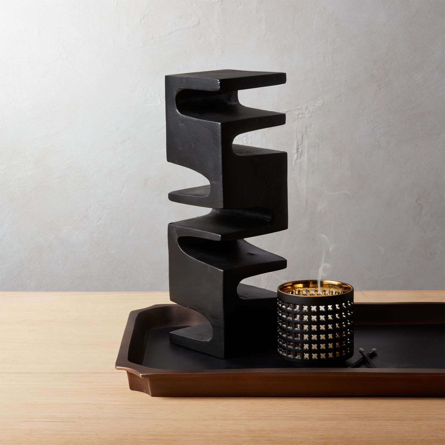 A tall black abstract sculpture by CB2.
