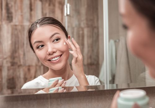 Smiling woman applies face cream in front of mirror