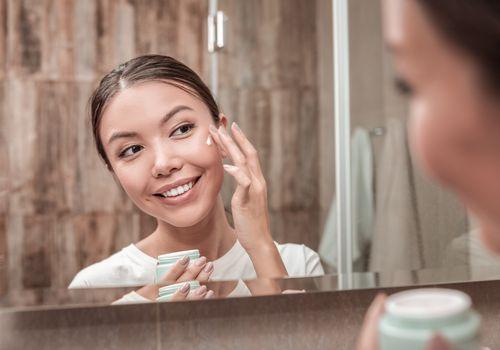 Mujer sonriente aplica crema para la cara delante del espejo