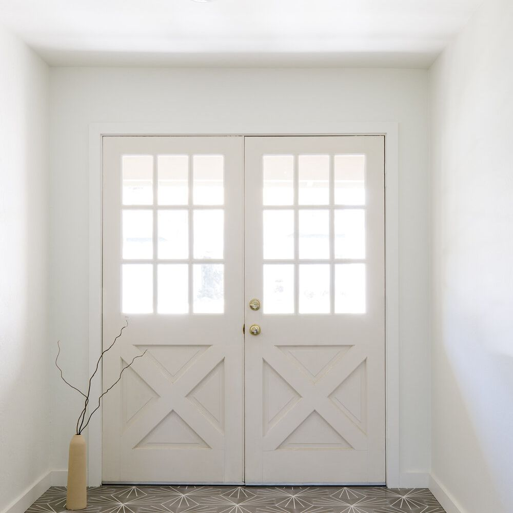 A foyer with white walls and ivory doors
