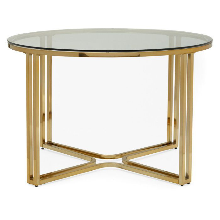 A round glass-top dining table with gold tone legs that meet on the floor.