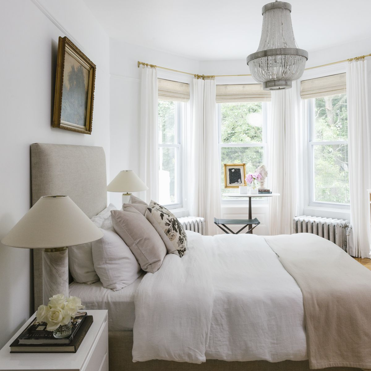 Soft neutral bedroom with chandelier.