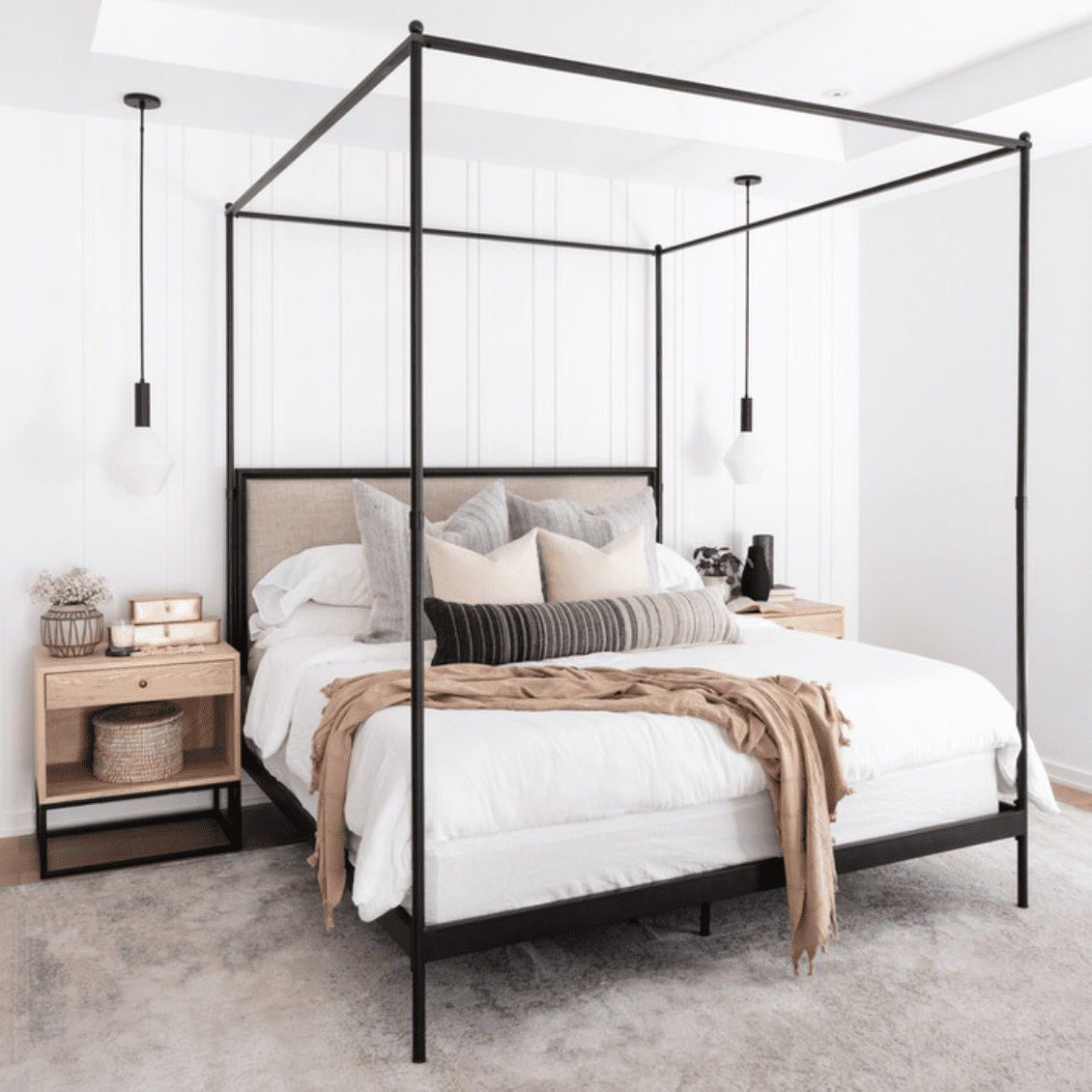 A bedroom with a black metal bed, white linens, and beige throw pillows and blankets