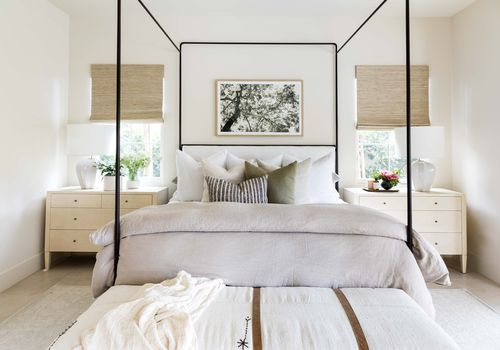 A light bedroom with a thin black canopy bed