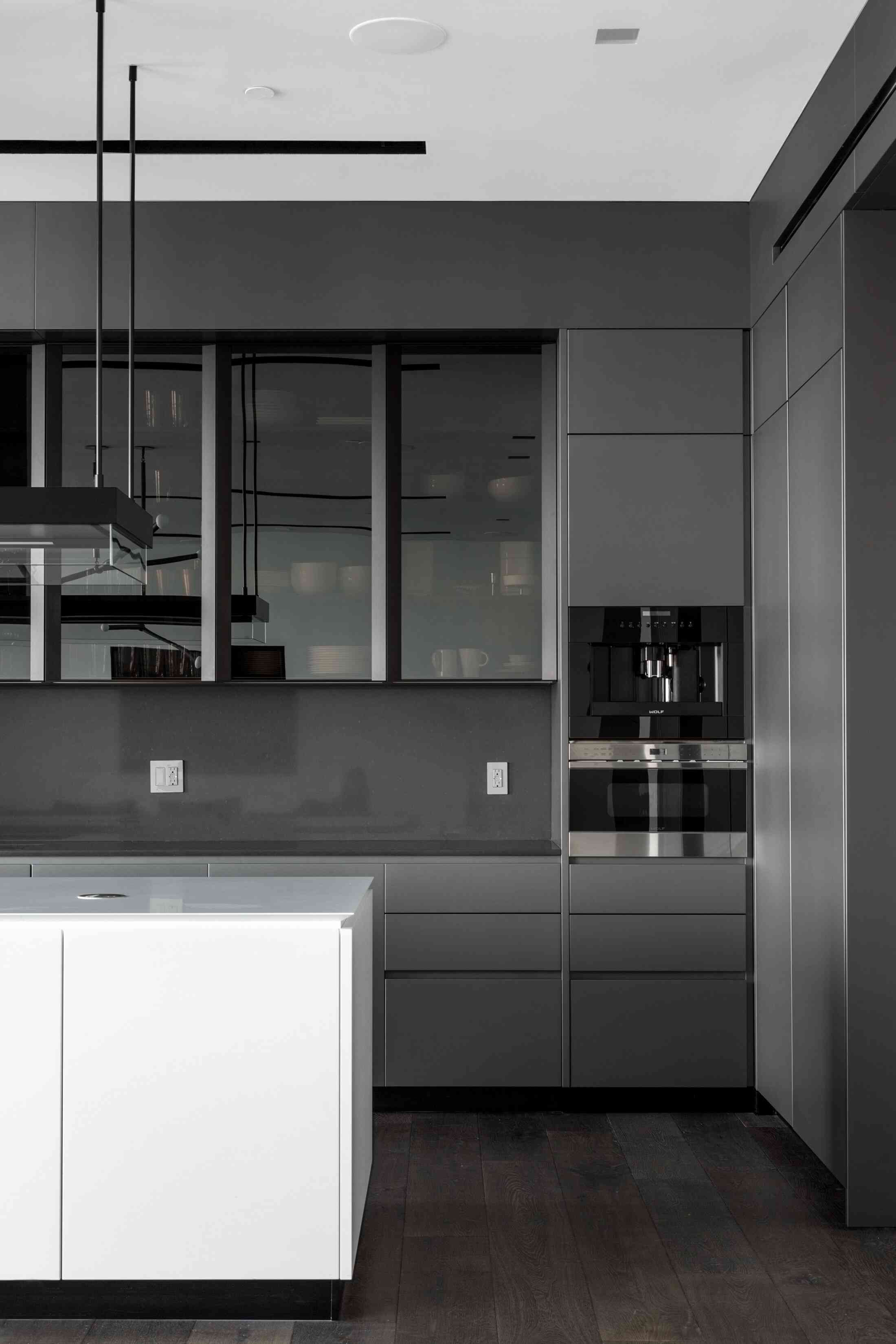 A kitchen with charcoal cabinets and black countertops