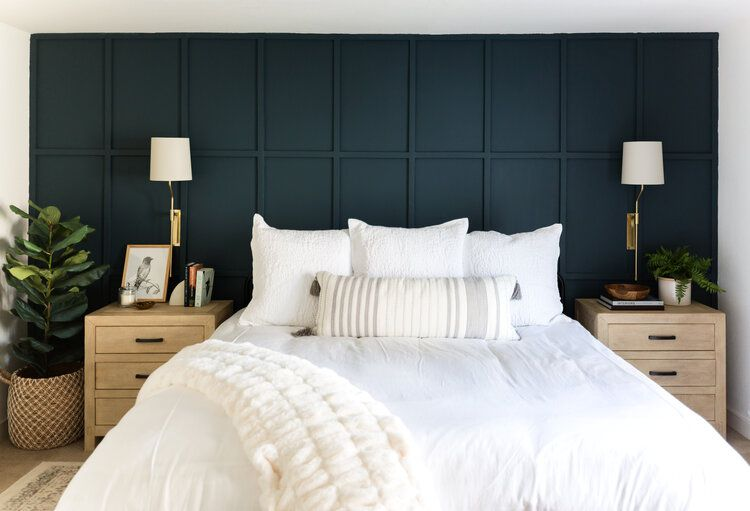 White bed in front of navy blue wall.