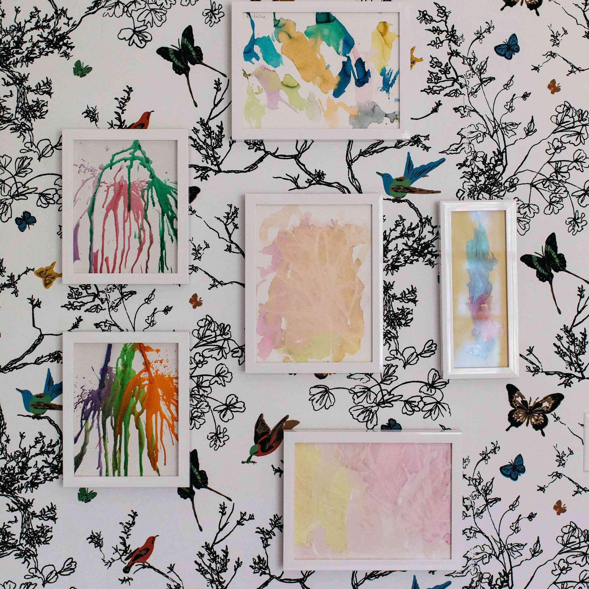 Watercolor art on wallpapered wall.