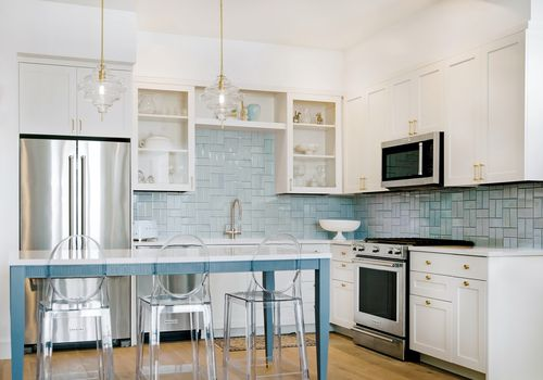 Renovated kitchen with blue tiled backsplash and clear barstools.